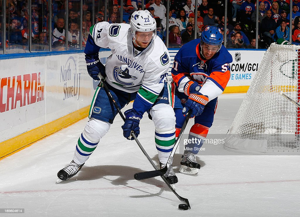 <a gi-track='captionPersonalityLinkClicked' href=/galleries/search?phrase=Alexander+Edler&family=editorial&specificpeople=882987 ng-click='$event.stopPropagation()'>Alexander Edler</a> #23 of the Vancouver Canucks controls the puck in front of <a gi-track='captionPersonalityLinkClicked' href=/galleries/search?phrase=Frans+Nielsen&family=editorial&specificpeople=634894 ng-click='$event.stopPropagation()'>Frans Nielsen</a> #51 of the New York Islanders at Nassau Veterans Memorial Coliseum on October 22, 2013 in Uniondale, New York. The Canucks defeated the Islanders 5-4 in overtime.