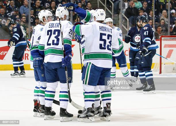 Alexander Edler of the Vancouver Canucks gets congratulated by teammates Brock Boeser and Bo Horvat after scoring a first period goal against the...