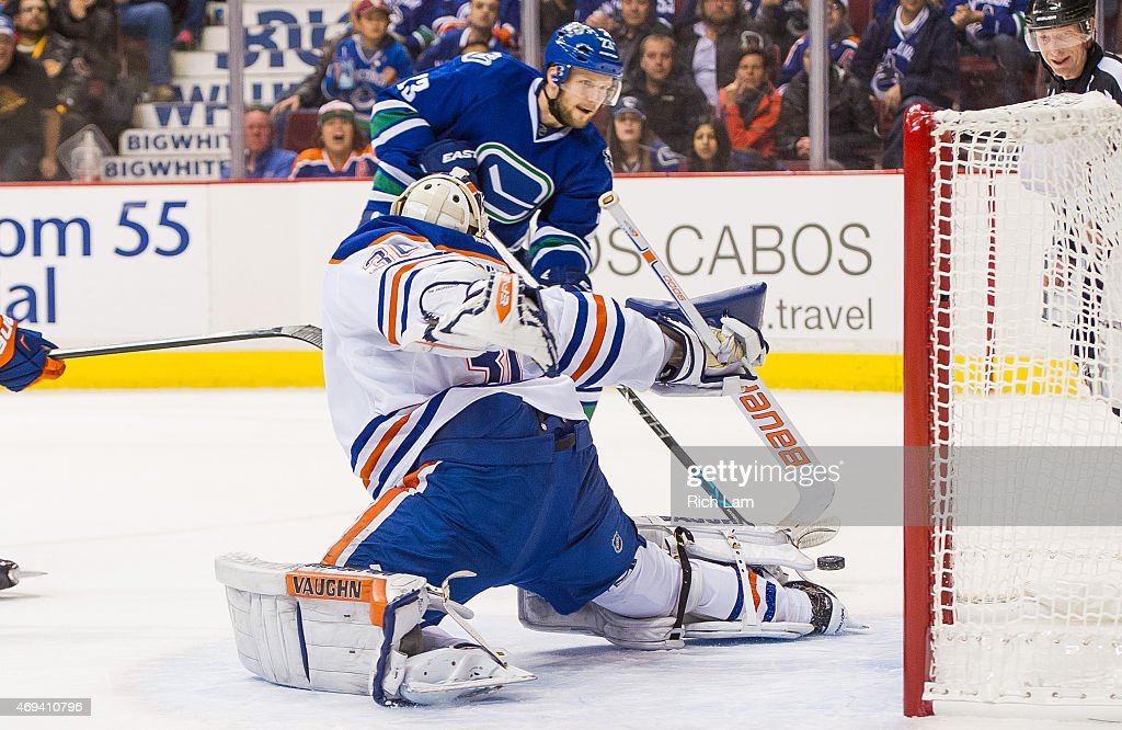 Alexander Edler of the Vancouver Canucks scores the game winning goal in overtime against goalie Ben Scrivens of the Edmonton Oilers to win 65 in NHL...