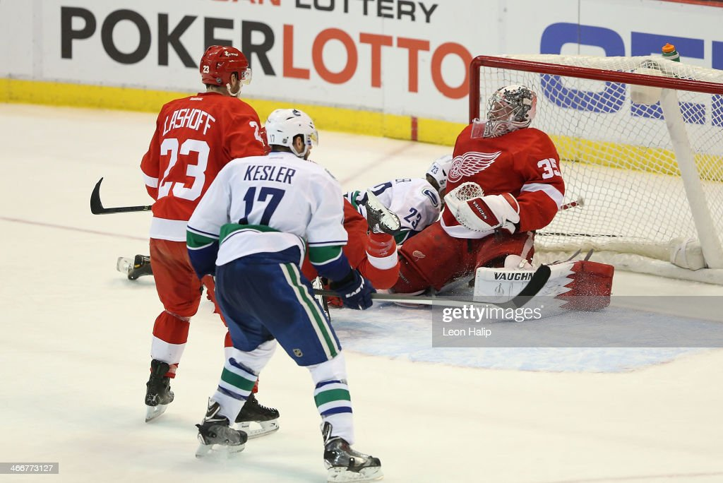 <a gi-track='captionPersonalityLinkClicked' href=/galleries/search?phrase=Alexander+Edler&family=editorial&specificpeople=882987 ng-click='$event.stopPropagation()'>Alexander Edler</a> #23 of the Vancouver Canucks skates into goalie Jimmy Howards #35 of the Detroit Red Wings during the second period of the game at Joe Louis Arena on February 3, 2014 in Detroit, Michigan. The Red Wings defeated the Canucks 2-0.