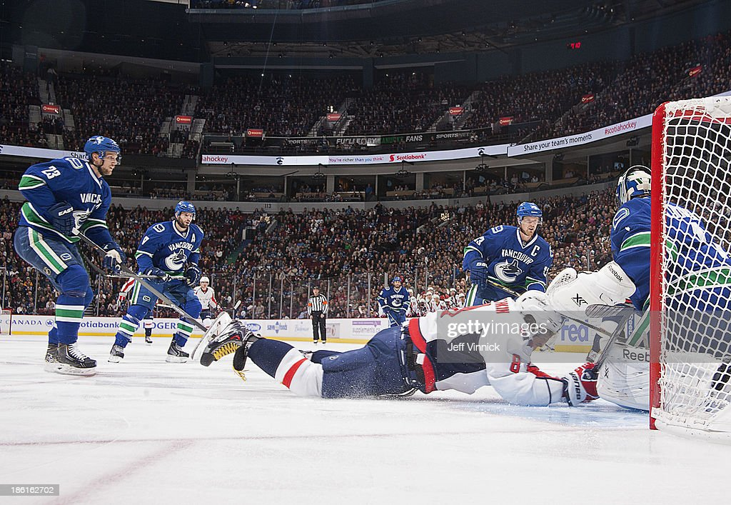 <a gi-track='captionPersonalityLinkClicked' href=/galleries/search?phrase=Alexander+Edler&family=editorial&specificpeople=882987 ng-click='$event.stopPropagation()'>Alexander Edler</a> #23 of the Vancouver Canucks trips Alex Ovechkin #8 of the Washington Capitals, who was awarded a penalty shot against <a gi-track='captionPersonalityLinkClicked' href=/galleries/search?phrase=Roberto+Luongo&family=editorial&specificpeople=202638 ng-click='$event.stopPropagation()'>Roberto Luongo</a> #1 of the Vancouver Canucks during their NHL game at Rogers Arena on October 28, 2013 in Vancouver, British Columbia, Canada.