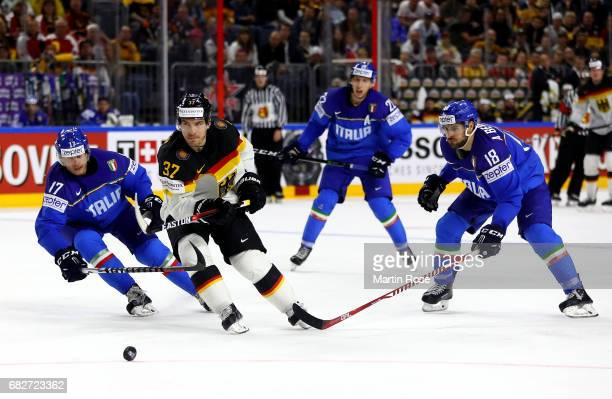 Alexander Egger of Italy challenges Patrick Reimer of Germany for the puck during the 2017 IIHF Ice Hockey World Championship game between Italy and...
