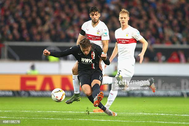 Alexander Esswein of Augsburg scores the opening goal against Emiliano Adrian Insúa Zapata of Stuttgart and his team mate Timo Baumgartl during the...