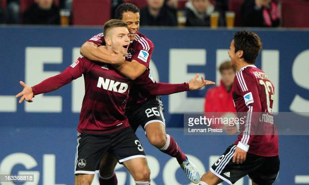 Alexander Esswein Timothy Chandler and Hiroshi Kiyotake of Nuernberg celebrate a goal during the Bundesliga match between FC Augsburg and 1 FC...