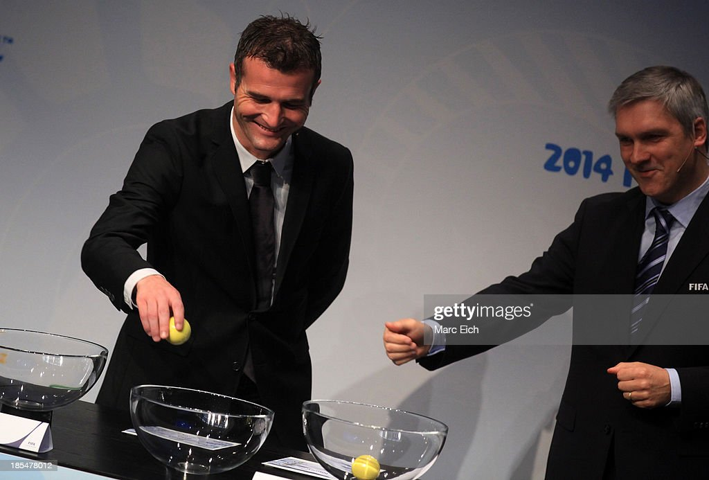 Alexander Frei (L), former Swiss international, picks up a ball during the FIFA World Cup 2014 European Zone Play-Off Match Draw at the FIFA headquarter on October 21, 2013 in Zurich, Switzerland.