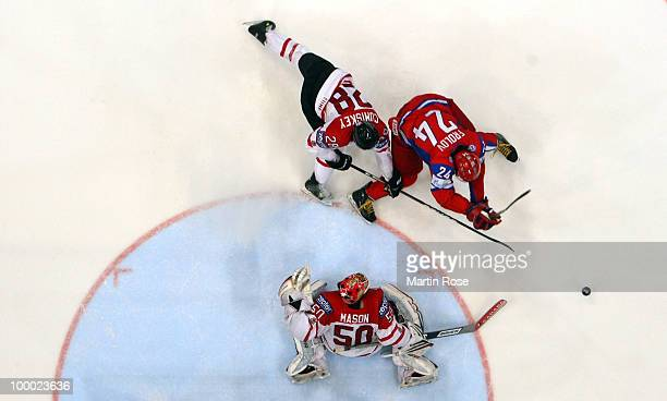 Alexander Frolov of Russia and Kyle Cumiskey of Canada battle for the puck during the IIHF World Championship quarter final match between Russia and...