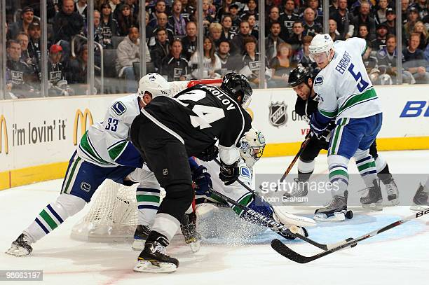 Alexander Frolov of the Los Angeles Kings drives to the net and scores a goal against Roberto Luongo and Henrik Sedin of the Vancouver Canucks in...