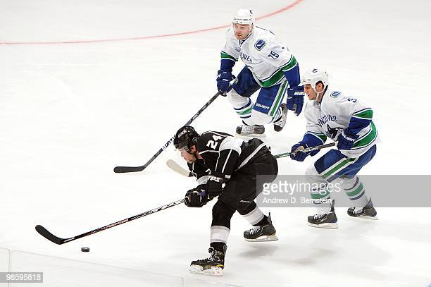 Alexander Frolov of the Los Angeles Kings skates with the puck against Kevin Bieksa and Aaron Rome of the Vancouver Canucks in Game Three of the...