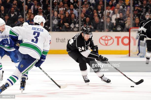 Alexander Frolov of the Los Angeles Kings skates with the puck against Kevin Bieksa of the Vancouver Canucks in Game Three of the Western Conference...