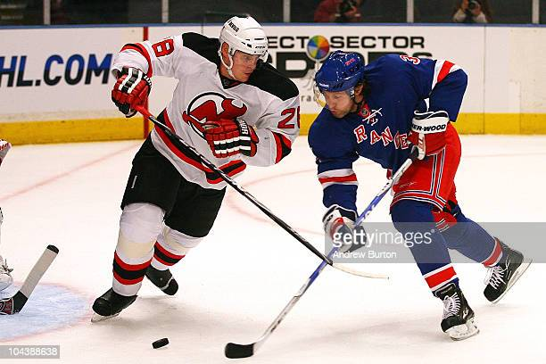 Alexander Frolov of the New York Rangers shoots the puck while Anton Volchenkov of the New Jersey Devils defends during a preseason game at Madison...