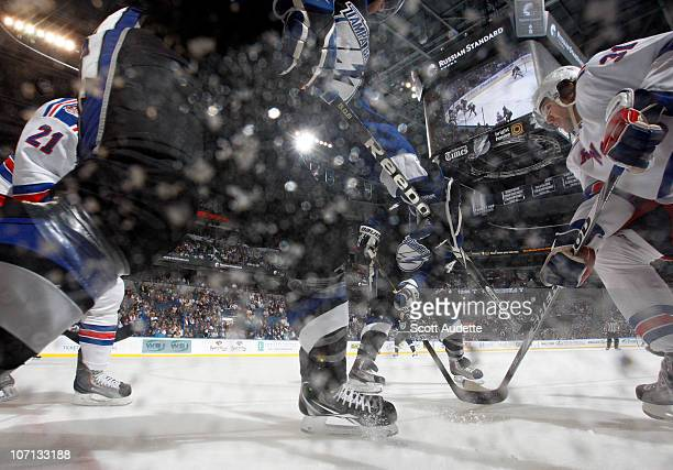 Alexander Frolov of the New York Rangers tries to the puck along the boards against Mattias Ohlund of the Tampa Bay Lightning during the first period...