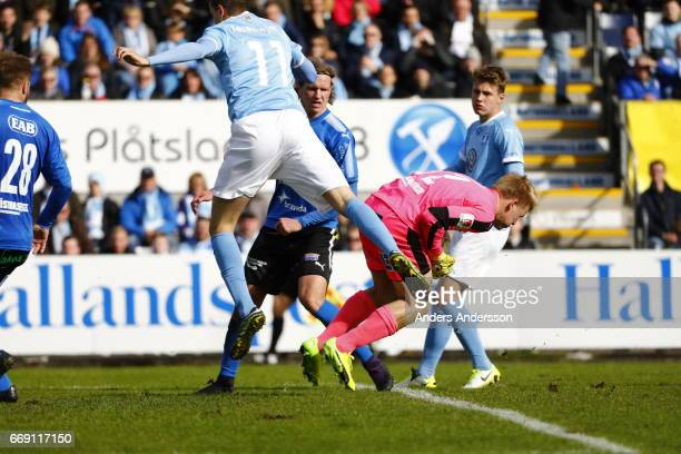 Alexander Jeremejeff of Malmo FF takes a shot and Isak Pettersson of Halmstad BK saves the shot during the Allsvenskan match between Halmstad BK and...