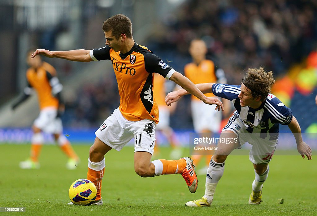 Alexander Kacaniklic of Fulham is tackled by Billy Jones of West Bromwich Albion during the Barclays Premier League match between West Bromwich Albion and Fulham at The Hawthorns, on January 1, 2013 in West Bromwich, England.