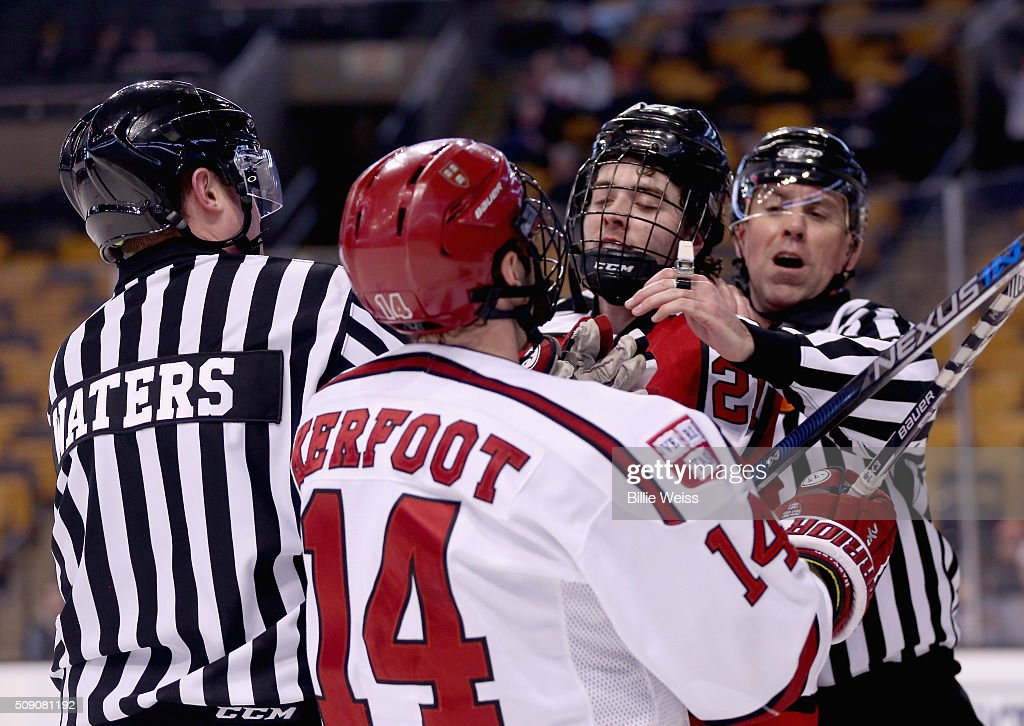 Alexander Kerfoot #14 of Harvard University fights with Nolan Stevens #21 of Northeastern University during the second period of the Beanpot Tournament consolation game at TD Garden on February 8, 2016 in Boston, Massachusetts.