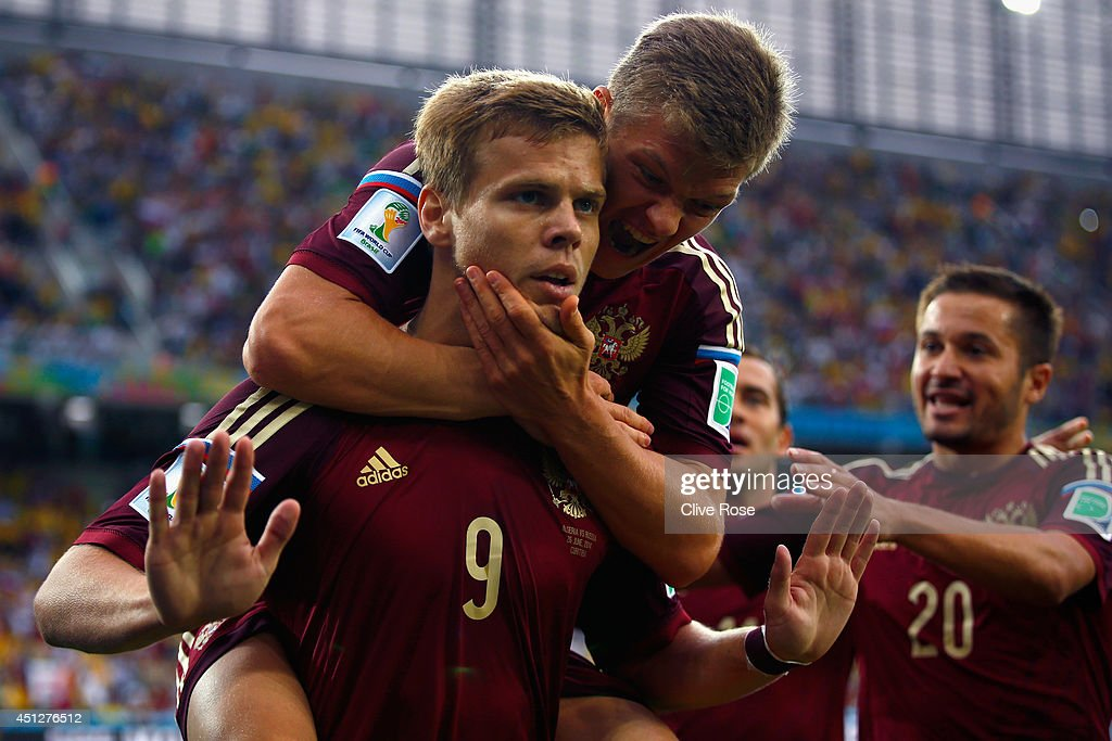 Alexander Kokorin of Russia celebrates scoring his team's first goal with teammate <a gi-track='captionPersonalityLinkClicked' href=/galleries/search?phrase=Oleg+Shatov&family=editorial&specificpeople=9633751 ng-click='$event.stopPropagation()'>Oleg Shatov</a> on his back during the 2014 FIFA World Cup Brazil Group H match between Algeria and Russia at Arena da Baixada on June 26, 2014 in Curitiba, Brazil.