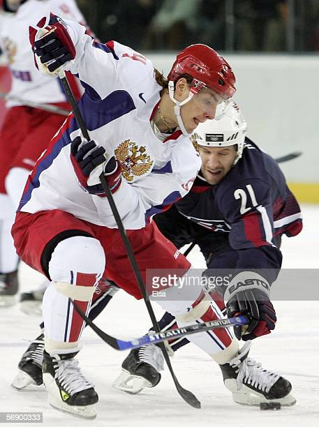 Alexander Korolyuk of Russia controls the puck against the defense of Mike Knuble of the United States during the men's ice hockey Preliminary Round...