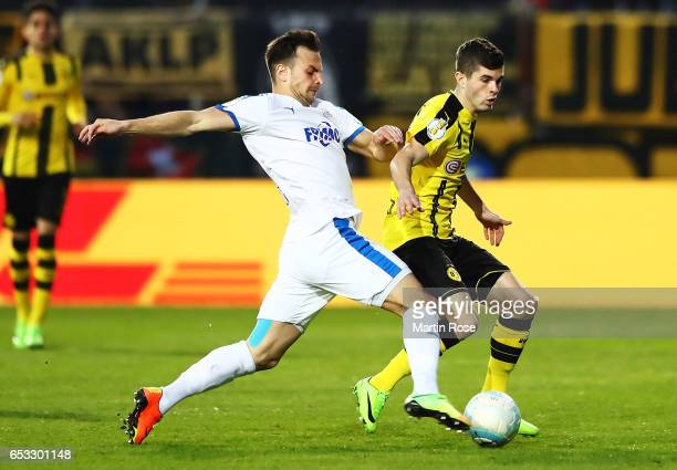 Alexander Langlitz of VfL Sportfreunde Lotte is challenged by Christian Pulisic of Borussia DortmundI during the DFB Cup quarter final between...