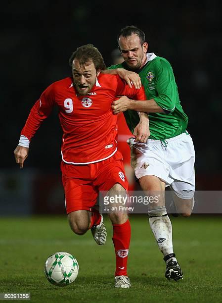 Alexander Lashili of Georgia holds off Stuart Elliott of Northern Ireland during the International Friendly match between Northern Ireland and...