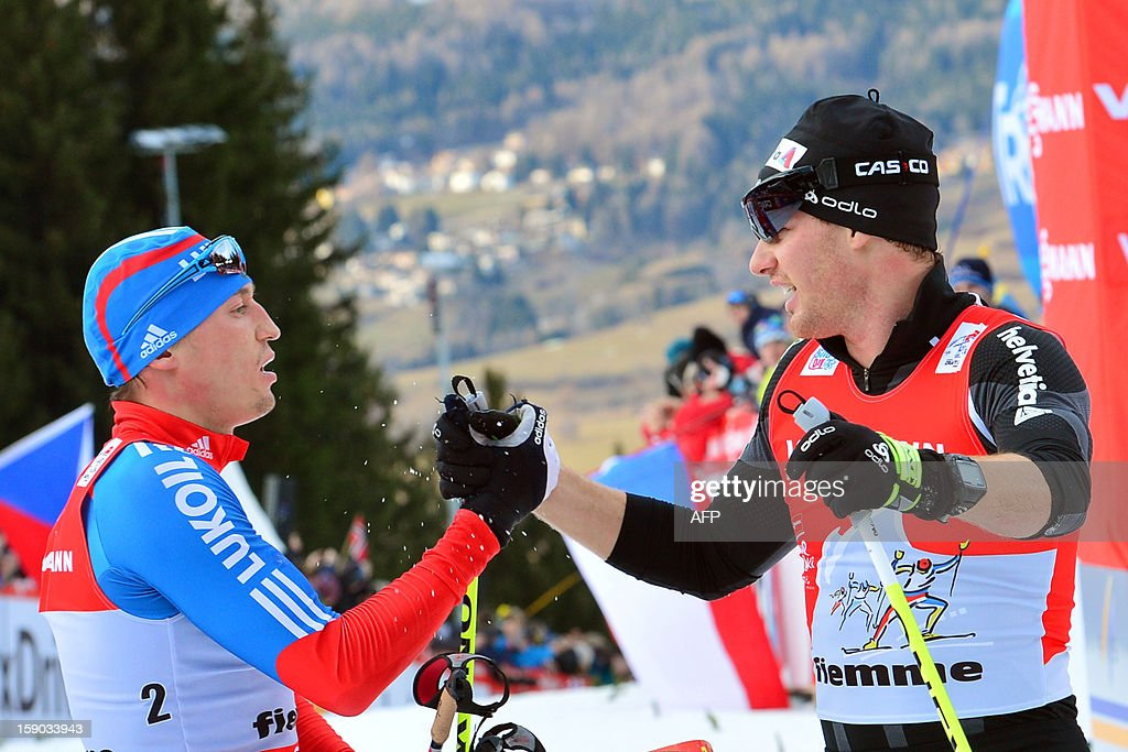 Alexander Legkov of Russia (L) shakes the hand of Swiss Dario Cologna of Swiss on the finish line during the men's nine km free final climb pursuit start race nine of the Tour de Ski in Val di Fiemme on January 6, 2013. Legkov won the race ahead of Cologna and Maxim Vylegzhnin of Russia .