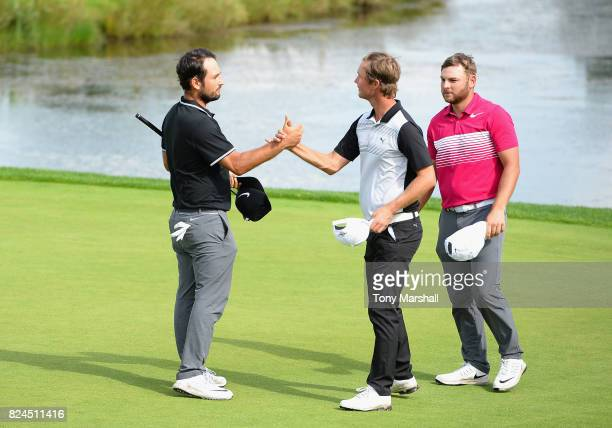 Alexander Levy of France shakes hands with Jens Fahrbring of Sweden at the end of their round during the Porsche European Open Day Four at Green...