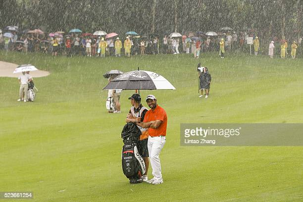 Alexander Levy of France shelters from the rain during the final round of the Shenzhen International at Genzon Golf Club on April 24 2016 in Shenzhen...
