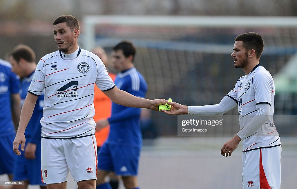 Alexander Maul (L) of Seligenporten passes his captain's armband to team-mate Marco Wiedmann of Seligenporten after receiving a red card during the Regionalliga Bayern match between FV Illertissen and SV Seligenporten at Voehlin-Stadion on November 24, 2012 in Illertissen, Germany.