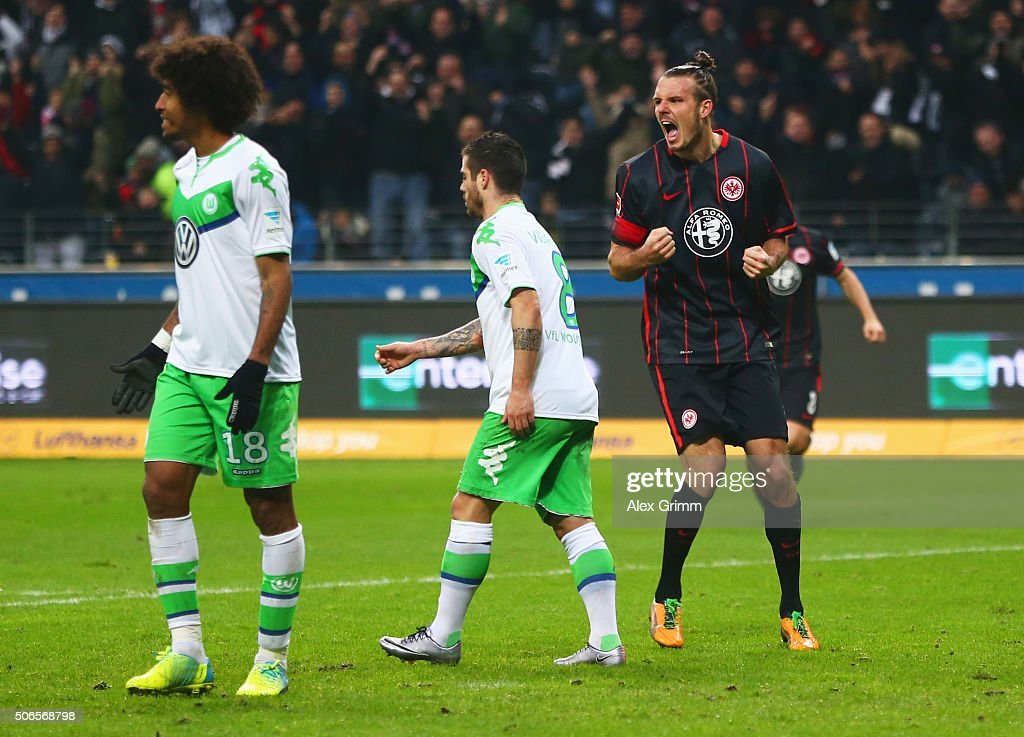 Alexander Meier of Eintracht Frankfurt (R) celebrates as he scores their first and equalising goal as Dante (18) and Vierinha of VfL Wolfsburg (8) look dejected during the Bundesliga match between Eintracht Frankfurt and VfL Wolfsburg at Commerzbank-Arena on January 24, 2016 in Frankfurt am Main, Germany.