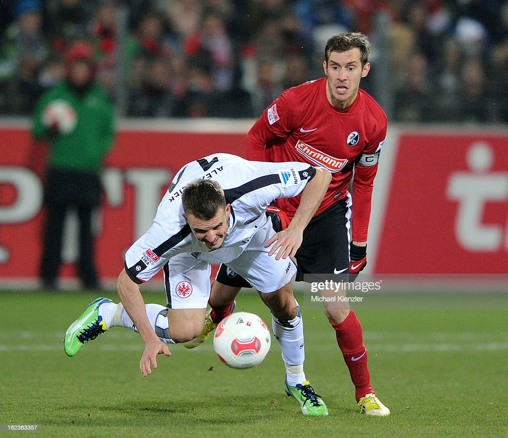 Alexander Meier of Frankfurt (L) is challenged by Julian Schuster of Freiburg during the Bundesliga match between SC Freiburg and Eintracht Frankfurt at MAGE SOLAR Stadium on February 22, 2013 in Freiburg, Germany.