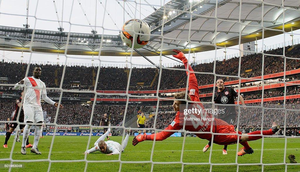 Alexander Meier of Frankfurt scores his team's first goal past Theodor Gebre Selassie of Bremen and goalkeeper Felix Wiedwald of Bremen during the...