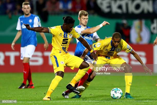 Alexander Muehlig of Kiel and Joseph Baffo and Louis Samson of Braunschweig battle for the ball during the DFB Cup first round match between Holstein...