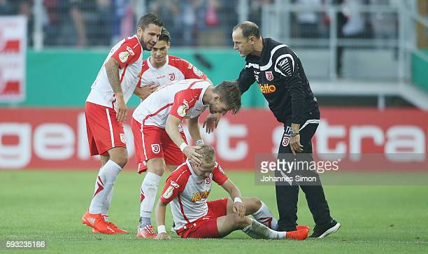 Alexander Nandzik of Regensburg celebrates with team mates and head coach Heiko Herrlich after scoring his team's first goal during the DFB Cup match...
