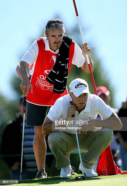 Alexander Noren of Sweden and his caddie Colin Byrne line up a putt on the 17th hole during the final round of The Omega European Masters at...