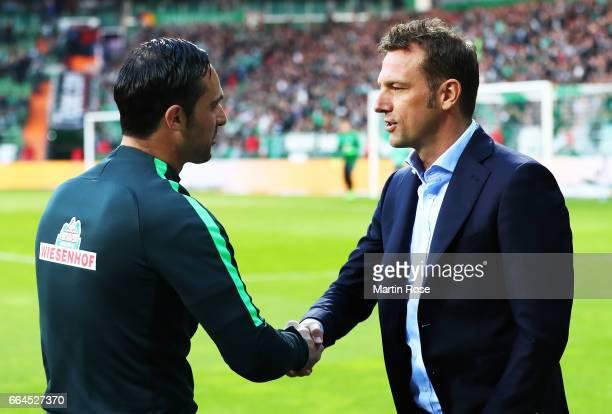 Alexander Nouri head coach of Werder Bremen shakes hands with Markus Weinzierl head coach of Schalke 04 before the Bundesliga match between Werder...