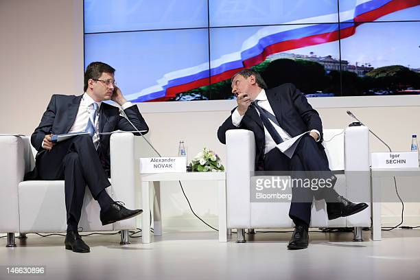 Alexander Novak Russia's energy minister left speaks with Igor Sechin president of OAO Rosneft during a conference session on day one of the Saint...