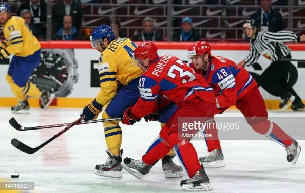 Alexander Perezhogin and Yevgeni Biryuko of Russia and Henrik Zetterberg of Sweden battle for the puck during the IIHF World Championship group S...