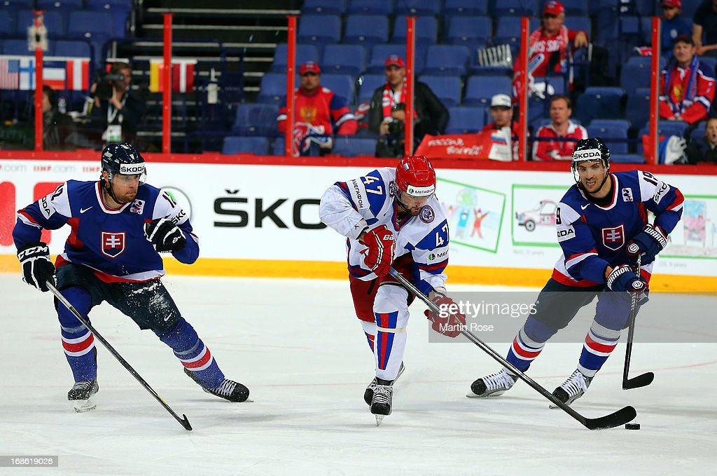 Alexander Radulov (C) of Russia and Michel Miklik (R) of Slovakia battle for the puck during the IIHF World Championship group H match between Slovakia and Russia at Hartwall Areena on May 12, 2013 in Helsinki, Finland.