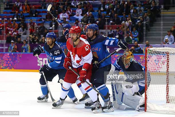 Alexander Radulov of Russia fights for position in front of the net with Kimmo Timonen Sami Vatanen and Tuukka Rask of Finland during the Men's Ice...