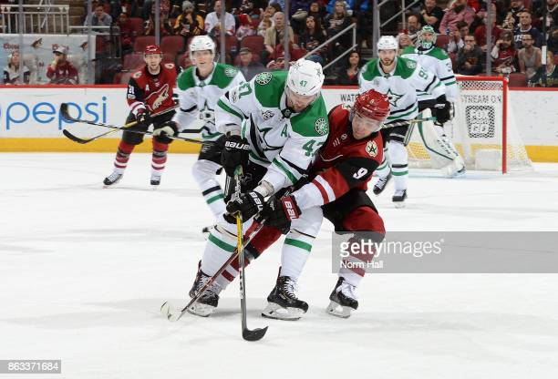 Alexander Radulov of the Dallas Stars and Clayton Keller of the Arizona Coyotes battle for the puck during the second period at Gila River Arena on...