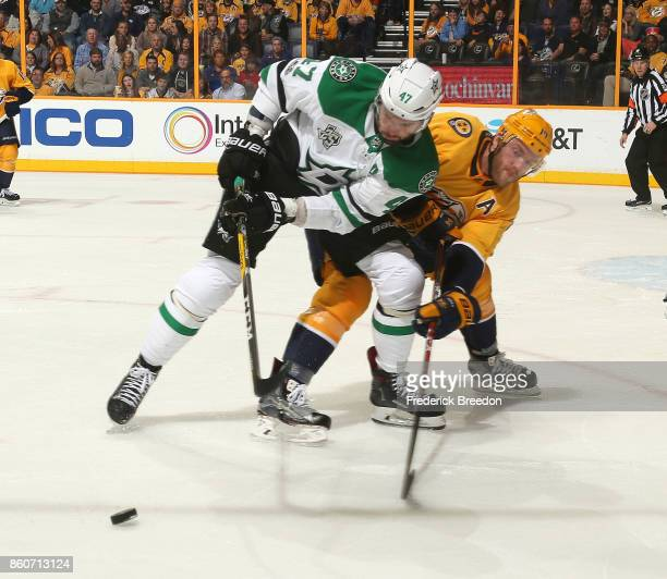 Alexander Radulov of the Dallas Stars and Mattias Ekholm of the Nashville Predators fight for a puck during the second period at Bridgestone Arena on...