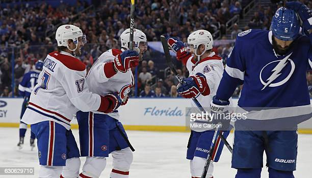 Alexander Radulov of the Montreal Canadiens center celebrates his goal with teammates Torrey Mitchell and Paul Byron as Jason Garrison of the Tampa...