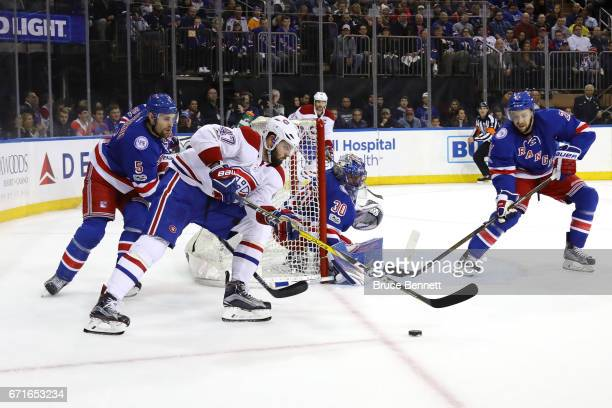 Alexander Radulov of the Montreal Canadiens shoots the puck against Derek Stepan and Henrik Lundqvist of the New York Rangers during the first period...