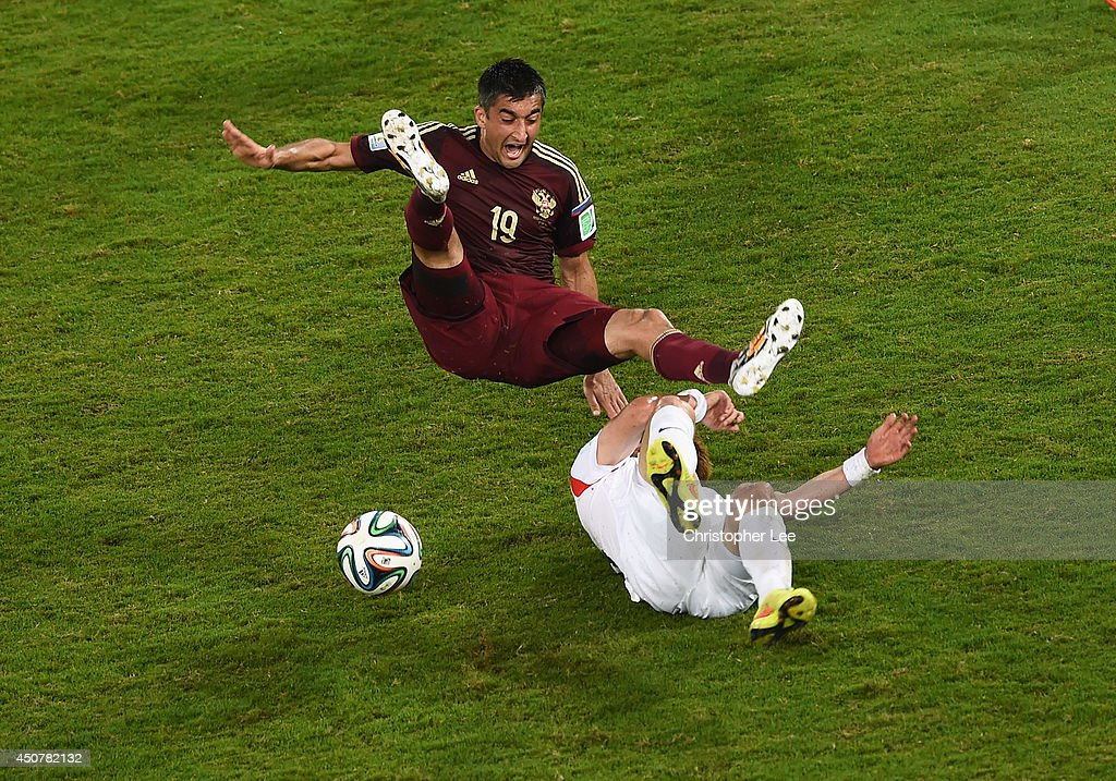 Alexander Samedov of Russia collides with Ki Sung-Yueng of South Korea during the 2014 FIFA World Cup Brazil Group H match between Russia and South Korea at Arena Pantanal on June 17, 2014 in Cuiaba, Brazil.