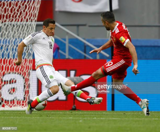 Alexander Samedov of Russia national team shoots to score a goal as Andres Guardado of Mexico national team defends during the Group A FIFA...