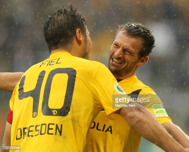 Alexander Schnetzler of Dresden jubilates with team mate Cristian Fiel after scoring the seventh goal during the DFB Cup first round match between SG...