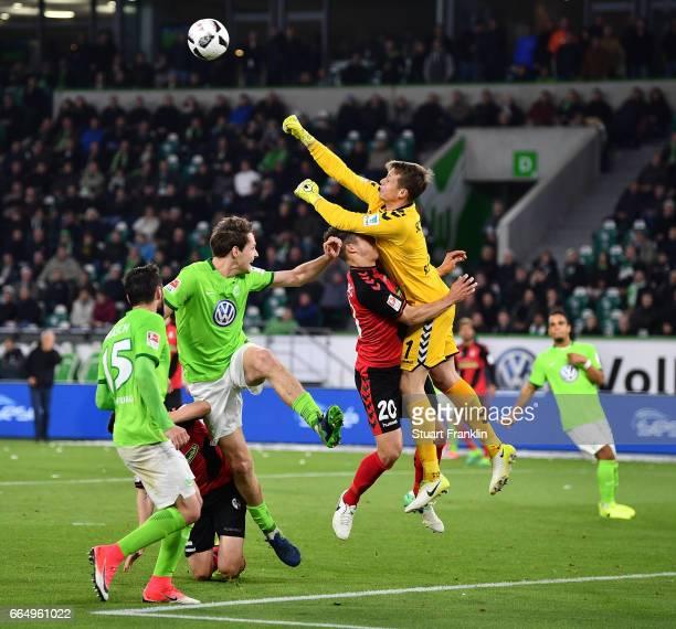 Alexander Schwolow of Freiburg punches a shot from Jannes Horn of Wolfsburg during the Bundesliga match between VfL Wolfsburg and SC Freiburg at...