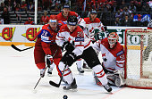 Alexander Semin of Russia and Kyle Cumiskey of Canada battle for the puck during the IIHF World Championship quarter final match between Russia and...