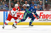 Alexander Semin of the Carolina Hurricanes and Alexander Edler of the Vancouver Canucks skate up ice during their NHL game against the Vancouver...