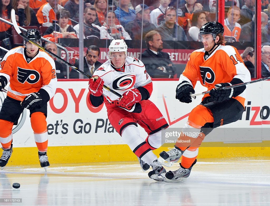 Alexander Semin #28 of the Carolina Hurricanes and Sean Couturier #14 of the Philadelphia Flyers collide while going for the puck at the Wells Fargo Center on February 9, 2013 in Philadelphia, Pennsylvania. The Flyers won 4-3 in overtime.