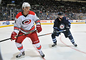 Alexander Semin of the Carolina Hurricanes and Zach Bogosian of the Winnipeg Jets keep an eye on the play along the boards during third period action...