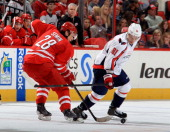 Alexander Semin of the Carolina Hurricanes battles for a loose puck against Dmitry Orlov of the Washington Capitals during their NHL game at PNC...